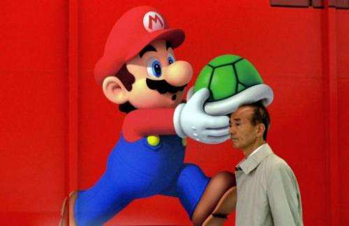 A man walks past a poster of Nintendo video game character Super Mario at an electronics shop in Tokyo on April 24, 2013