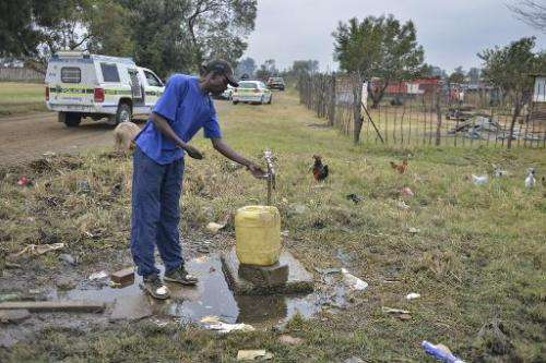 A man works a tap in the restive township of Gugulethu, near Cape Town, on May 6, 2014