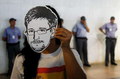 """A member of the Avaaz online community organization wears a """"Snowden"""" mask in Brasilia, on February 13, 2014"""