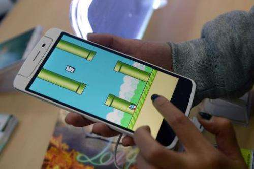 An employee plays the game Flappy Bird at a smartphone store in Hanoi on February 10, 2014