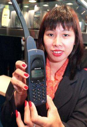 An Ericsson promoter shows the mobile phone R290 Satellite which requires one subscription for both cellular and satellite usage