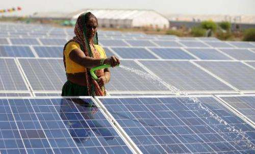 An Indian worker sprays water onto panels of India's first 1MW canal-top solar power plant at Chandrasan village of Mehsana dist