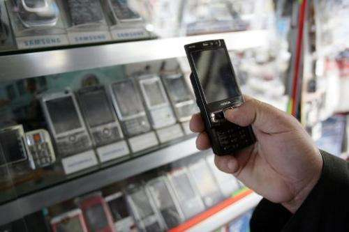 An Iraqi man checks a mobile phone at a shop in Baghdad on March 17, 2008