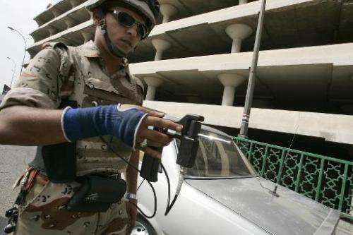 An Iraqi soldier uses an explosive detector-device at a checkpoint in central Baghdad, October 17, 2007