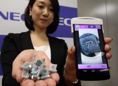 An NEC employee in Tokyo on November 10, 2014 displays fake products detectable with its new smartphone system
