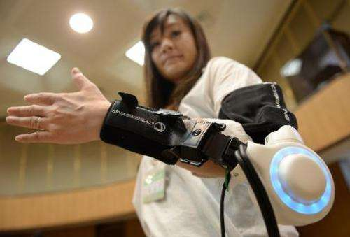 An official of Kawasaki City demonstrates a new powered exoskeleton to assist movement of an arm developed by Japan's robot suit