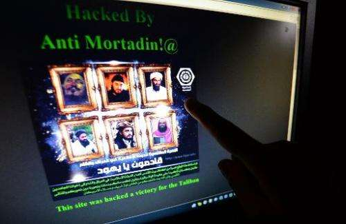 A Pakistani points at a computer screen showing the hacked official website of Rawalpindi police on May 15, 2014