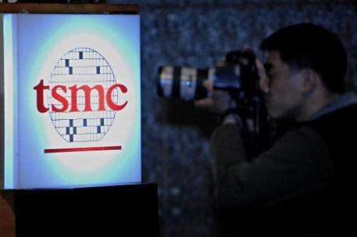A photographer takes a picture of Taiwan Semiconductor Manufacturing Company logo during a quarterly report meeting in Taipei on