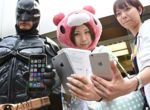 Apple fans show off their new iPhone 6 handsets at an Apple store in Ginza, Tokyo on September 19, 2014