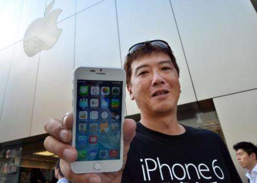 Apple fan Tetsuya Tamura holds a China made 'iPhone 6' outside an Apple store in Tokyo on September 12, 2014