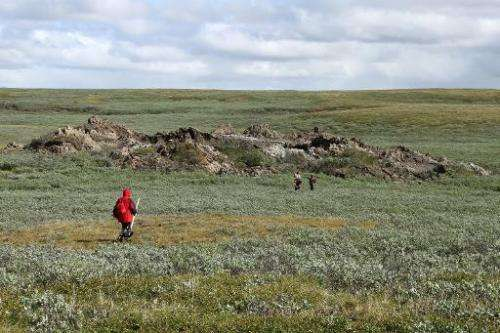 A scientist walks near a mysterious crater in the permafrost north of regional capital Salekhard in the Yamalo-Nenets region, 2,