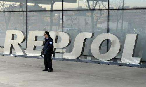 A security guard stands outside the main entrance to Spanish oil giant Repsol's headquarters in Madrid on January 24, 2014