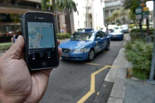 A smartphone displays the Uber app of the timing and availability of taxis within the area at Raffles place financial district i