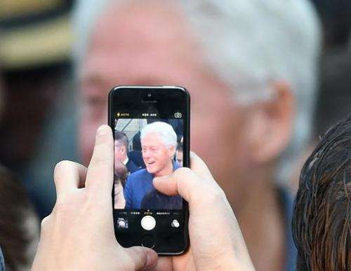 A supporter takes photos of former U.S. President Bill Clinton on a cell phone during a get-out-the-vote rally on October 28, 20