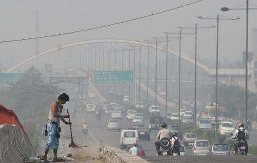 A sweeper cleans a flyover as smog covers the capital's skyline, morning after celebrations for the Diwali festival, in New Delh