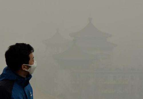A tourist wearing a face mask climbs Jingshan Hill beside the Forbidden City as heavy air pollution shrouds Beijing