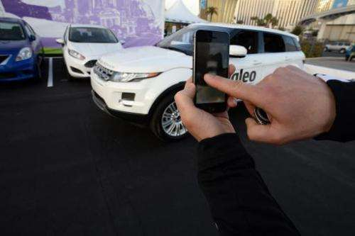 A Valeo representative swipes his finger across an iPhone to initiate a self parking demonstration at the 2014 International CES