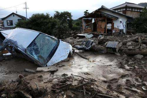 A vehicle is buried in mud one day after a landslide hit a residential area in Hiroshima, western Japan on August 21, 2014