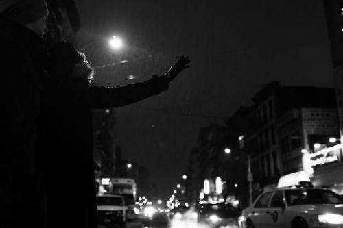 A woman attempts to hail a taxi in New York City on February 13, 2014