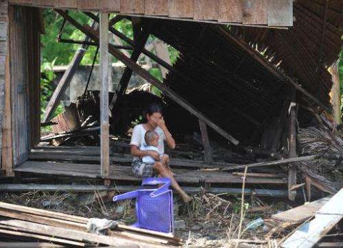 A woman sits with her daughter in her collapsed house on October 31, 2010 in Tumalei village, Metawai islands, Indonesia, six da