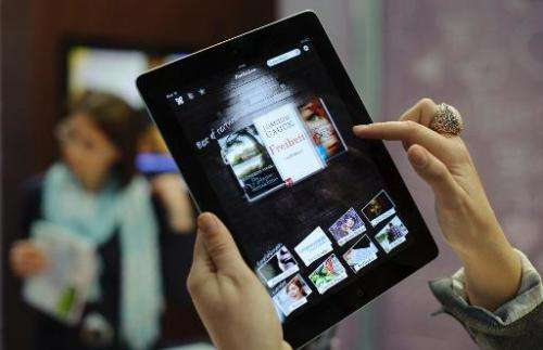 A woman uses an eBook app on an Apple iPad at the Leipzig Book Fair on March 15, 2012