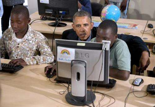 Barack Obama sits at a computer as he tours a classrom at the Desmond Tutu HIV Foundation Youth Centre in Cape Town, South Afric