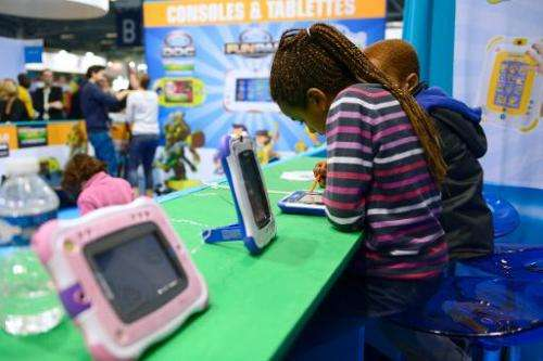 """Children play with digital tablets on October 19, 2013, during the """"Kidexpo"""" show at the Porte de Versailes exhibition"""