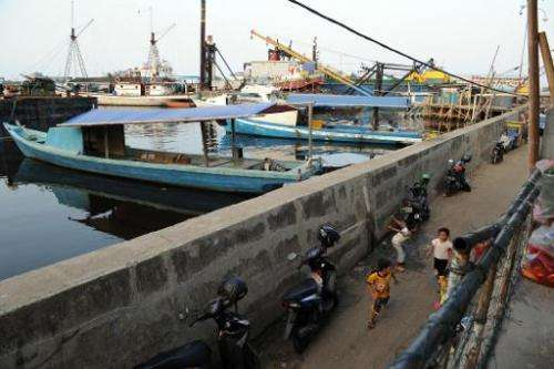 Children residing in the slum area play along a dyke as construction of the Jakarta sea wall begins, October 9, 2014