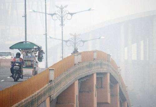 Commuters cross a bridge as thick haze blankets Pekanbaru in Indonesia on September 16, 2014