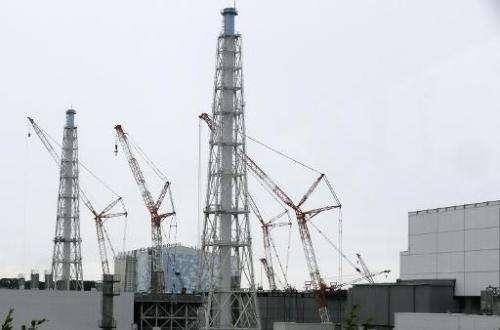 Cranes work at the tsunami-crippled Tokyo Electric Power Co.'s Fukushima Daiichi Nuclear Power Plant in Okuma, Fukushima Prefect
