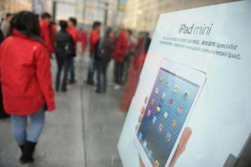 Customers are seen waiting for an Apple store to open in Shanghai, on December 7, 2012