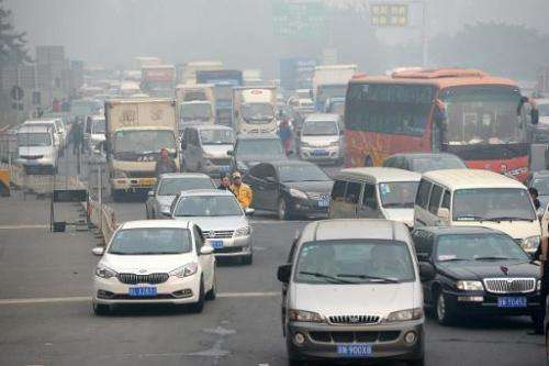 Drivers wait at the entrance of a highway in Beijing as most of the highways were closed due to the heavy smog on October 9, 201