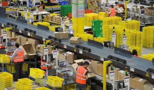 Employees work at an Amazon logistics center on March 26, 2014 in Leipzig, eastern Germany