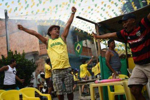 Fans of Brazil react at the end of the match in Porto Seguro on June 28, 2014