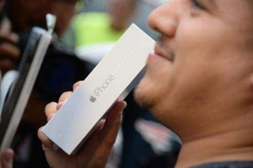 First in line Francisco Naranjo holds up his new iPhone 6 Plus, outside the Apple store in Pasadena, California on the first day