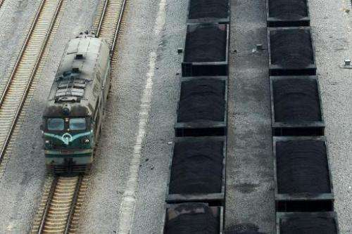 Freight cars (right) filled with coal parked inside a coal mining facility in Huaibei, in northern China's Anhui province on Mar