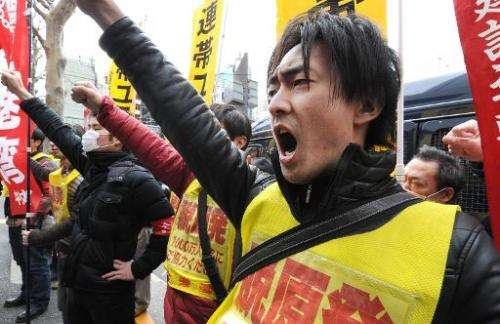 Fukushima nuclear workers and their supporters shout slogans outside the headquarters of Tokyo Electric Power Company (TEPCO) on