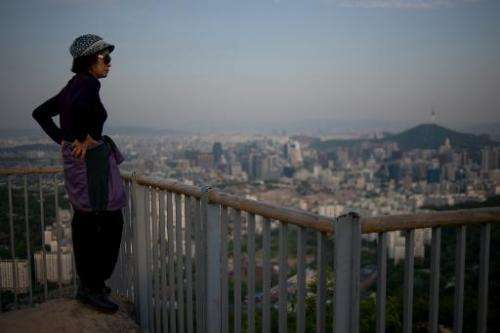 In a photo taken on May 9, 2014, a South Korean woman stands before the Seoul city skyline at dusk
