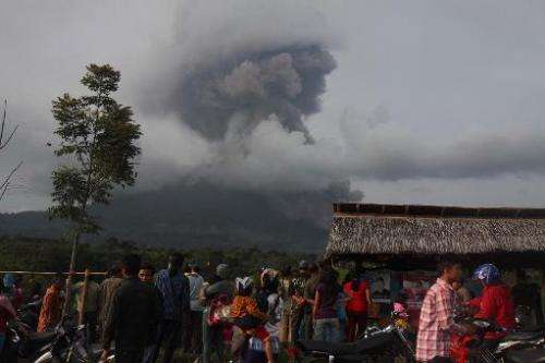 Indonesians look at the volcanic ash spewing up into the air from Mount Sinabung as it erupts in Karo, North Sumatra, on January