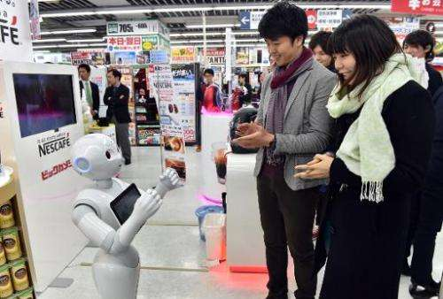 Japanese telecom giant Softbank's humanoid robot Pepper introduces customers to Nestle's coffee machines at an electric shop in