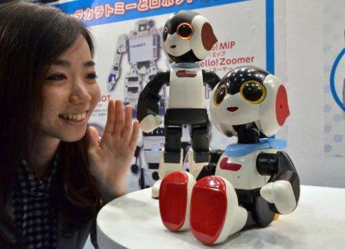 """Japan's toy maker Tomy employee enjoys a conversation with a little humanoid robot """"Robi jr."""" which can speak some 1,0"""