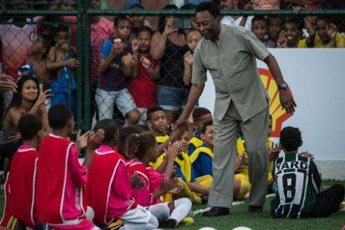 Legendary Brazilian former football player Pele greets children during the inauguration ceremony of the new football pitch insta