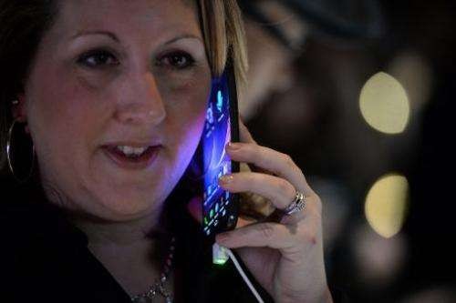 LG representative Amy Sanchez holds LG's new G Flex curved screen smartphone during the LG press conference at the Mandalay Bay