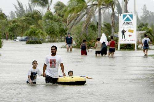 Local residents wade through flooded streets due to Hurricane Katrina, on August 26, 2005, in Miami, Florida