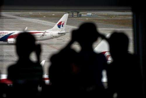 Malaysian children are silhouetted as they watch a Malaysia Airlines (MAS) plane taxi on the runway at Kuala Lumpur Internationa