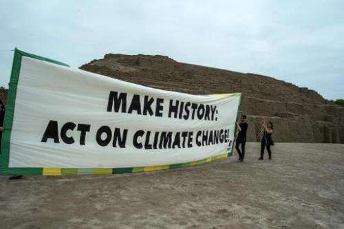 Members of Oxfam international organization hold a banner at the archaeological site of Huaca Pucllana in Lima on November 29, 2
