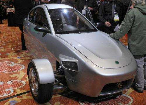 Members of the media inspect a prototype of three-wheeled car, the brainchild of Paul Elio, founder and CEO of Elio Motors, on t