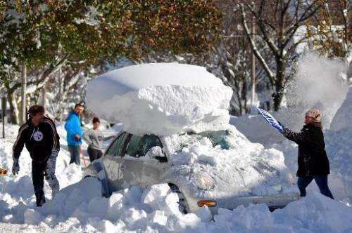 Michael Palmer and Carin Schultz work to clear her car of snow and remove it from Union street on November 20, 2014 in the subur