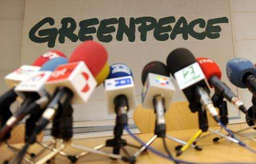 Microphones stand on a table in front of a Greenpeace logo before a press conference on January 4, 2010 in Madrid
