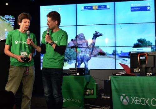 Microsoft Japan employees demonstrate video game console Xbox One, at a video game cafe in Tokyo, on September 3, 2014, on the e